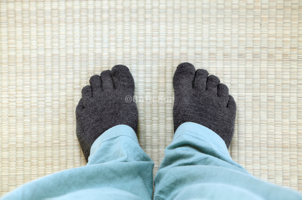 person wearing Japanese five finger socks on a tatami mat floor