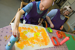 Day Service user with learning disabilities using sponge shapes to paint,