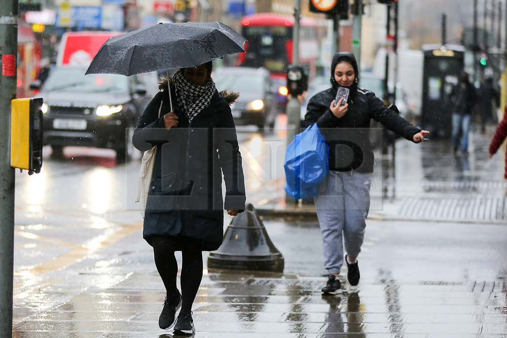 © Licensed to London News Pictures. 14/11/2020. London, UK. A woman wearing a face covering shelters from rain underneath an umbrella in north London. The Met Office has issued a yellow weather warning for the UK for heavy rain and strong winds, as up to 20 days worth of rain is expected to fall in the next few days. Photo credit: Dinendra Haria/LNP