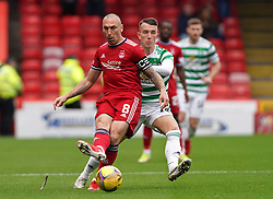 Aberdeen's Scott Brown (left) and Celtic's David Turnbull battle for the ball during the cinch Premiership match at Pittodrie Stadium, Aberdeen. Picture date: Sunday October 3, 2021.