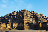 Borobudur is a Mahayana Buddhist Temple in Magelang, Central Java.  The monument consists of six square platforms topped by three circular one, and is festooned with 2,672 bas-relief panels and 504 Buddha statues.  The main dome is empty, located at the center of the top platform, though it is surrounded by 72 Buddha statues seated inside a perforated stupas.  Borobudur was constructed in the 9th century and abandoned after the 14th century because of the decline of Buddhism in Java, and the Javanese conversion to Islam.  Worldwide knowledge of its existence was rekindled in 1814 by Sir Thomas Stamford Raffles, at that time the British ruler of Java, who was told of its location by local Indonesians. Borobudur has since been preserved through several restorations and was declared a UNESCO World Heritage Site.  Borobudur is the largest Buddhist temple in the world built over 1200 years ago.
