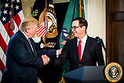 President Donald Trump shakes hands with Treasury Secretary Steven Mnuchin before signing one executive order and two presidential memoranda on tax and Wall Street regulations in Washington, District of Columbia, U.S., on Friday, April 21, 2017. This was President Trump's first visit to the Treasury Department.