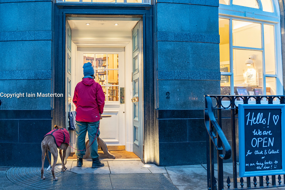 Edinburgh, Scotland, UK. 17 January 2020. On first Sunday after tightening of national lockdown rules in Scotland a customer waits outside Topping & Co bookshop to use click & collect service. Iain Masterton/Alamy Live News