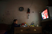 A little boy watches cartoons on TV in his Tulou home in Fujian.