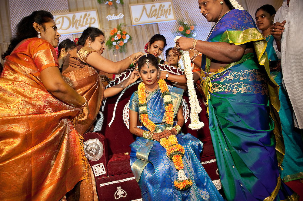 The bride is adorned with a flower garland and more gifts are given.