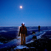 Nastya rests under the moonlight as she treks across frozen Lake Baikal in Siberia, Russia. (Second night)..They are a group of five people: Justin Jin (Chinese-British), Heleen van Geest (Dutch), Nastya and Misha Martynov (Russian) and their Russian guide Arkady. .They pulled their sledges 80 km across the world's deepest lake, taking a break on Olkhon Island. They slept two nights on the ice in -15c. .Baikal, the world's largest lake by volume, contains one-fifth of the earth's fresh water and plunges to a depth of 1,637 metres..The lake is frozen from November to April, allowing people to cross by cars and lorries.