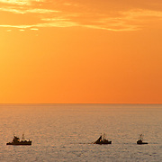 Three fishing boats off Monhegan Island at sunrise