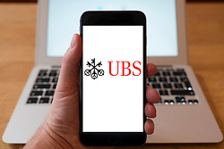 Using iPhone smartphone to display logo of UBS global financial services company