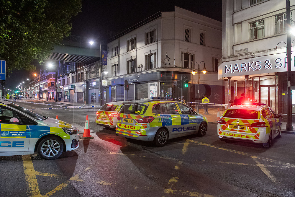 © Licensed to London News Pictures. 21/07/2021. London, UK. Police vehicles at the scene following a fatal stabbing on Brixton Road, Brixton. Metropolitan Police Service (MPS) were called at 20:18BST to reports of an assault close to Brixton Underground Station. Despite efforts from police officers, paramedics from London Ambulance Service (LAS) and London's Air Ambulance the man was pronounced dead at the scene at the 20:45BST. Photo credit: Peter Manning/LNP