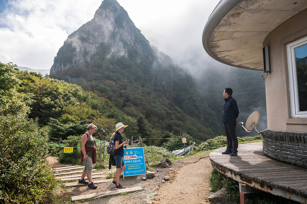 Hallasan National Park, South Korea - September 16, 2019: Two foreigners hiking the Gwaneumsa Trail in Hallasan National Park reach a trail shelter. Located on Jeju Island, Hallasan is the highest mountain in South Korea.