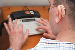 Man with hearing impairment using minicom.