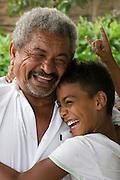 A boy hugs a man in Jardim São Marcos favela, Cubatão