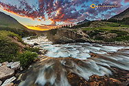 Vivid sunrise clouds over Swiftcurrent Falls in Glacier National Park, Montana, USA