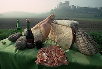 October 1989, Parma, Italy --- Locally produced prosciutto, salami, parmesean, and wines stand on a table in a field below Castle Torrechiara in the countryside near Parma, Italy. --- Image by © Owen Franken/CORBIS
