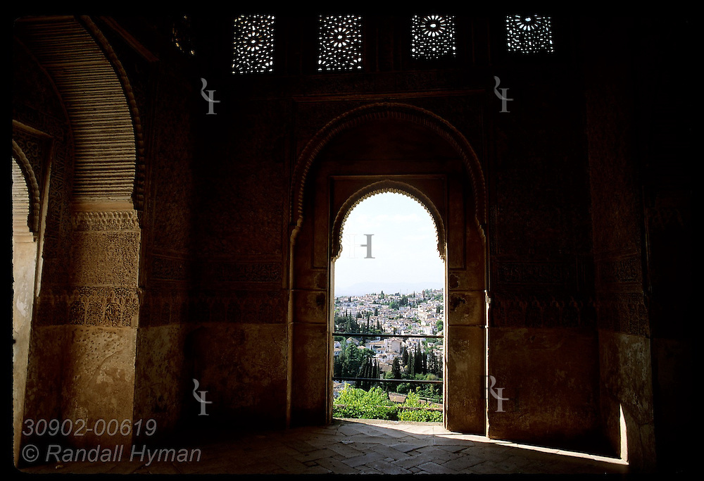 Moorish arches frame view of Granada at Generalife's Sala Regia, country estate of Nasrid kings. Spain