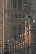 A detail of neo-Gothic architecture of the British Houses of Parliament, seat of the UK's government, on 17th January 2017, in London England. The Elizabeth Tower (previously called the Clock Tower) named in tribute to Queen Elizabeth II in her Diamond Jubilee year – was raised as a part of Charles Barry's design for a new palace, after the old Palace of Westminster was largely destroyed by fire on the night of 16 October 1834. The new Parliament was built in a Neo-gothic style. Although Barry was the chief architect of the Palace, he turned to Augustus Pugin for the design of the clock tower. It celebrated its 150th anniversary on 31 May 2009. The tower was completed in 1858 and has become one of the most prominent symbols of both London and England.