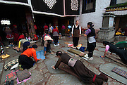 """Tibetan pilgrims at the sacred Jokhang Temple (""""House of the Lord"""") in Lhasa,the holiest site in Tibetan Buddhism. It draws thousands of prostrating Tibetan pilgrims, as well as curious foreign tourists every year. <br /> <br /> The Jokhang Temple was founded in 647 by King Songtsen Gampo (r.617-49), the first ruler of a unified Tibet, and his two foreign wives who are credited with bringing Buddhism to Tibet. The king's first wife, Princess Bhrikuti,the sister of the Nepalese king, while his second wife, Princess Wencheng was the niece or daughter of the Chinese emperor."""