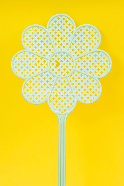 a green fly swatter in the form of a flower against a yellow background