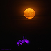 A flood-lit St Michael's Mount glows in the blackness whilst a huge Harvest Moon slowly rises behind.
