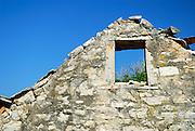 Broken stone wall and window, derelict building, village of Vrboska, island of Hvar, Croatia
