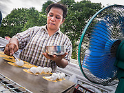 "27 NOVEMBER 2012 - BANGKOK, THAILAND:  A food vendor prepares snacks on a street in front of Wat Saket, during the temple's fair in Bangkok. Wat Saket, popularly known as the Golden Mount or ""Phu Khao Thong,"" is one of the most popular and oldest Buddhist temples in Bangkok. It dates to the Ayutthaya period (roughly 1350-1767 AD) and was renovated extensively when the Siamese fled Ayutthaya and established their new capitol in Bangkok. The temple holds an annual fair in November, the week of the full moon. It's one of the most popular temple fairs in Bangkok. The fair draws people from across Bangkok and spills out in the streets around the temple.   PHOTO BY JACK KURTZ"