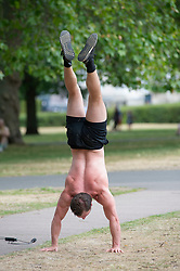 ©Licensed to London News Pictures 15/06/2020<br /> Greenwich, UK. A muscular young man doing a handstand in the park. People out and about in Greenwich park, Greenwich, London enjoying the warm sunny weather and Coronavirus lockdown freedom. Photo credit: Grant Falvey/LNP