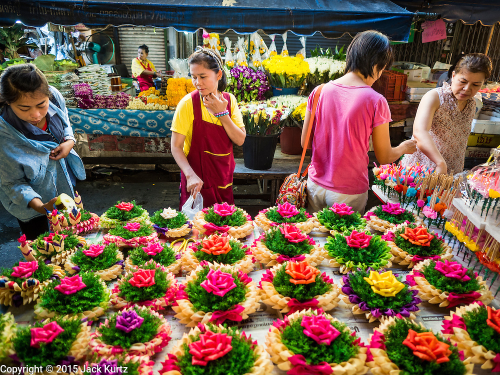 """24 NOVEMBER 2015 - BANGKOK, THAILAND:  People shop for """"krathongs"""" in Bang Chak Market. Krathongs are small boats Thais float in canals and bodies of water, on Loy Krathong, a Buddhist holiday on the full moon in November.  The Bang Chak Market serves the community around Sois 91-97 on Sukhumvit Road in the Bangkok suburbs. About half of the market has been torn down. Bangkok city authorities put up notices in late November that the market would be closed by January 1, 2016 and redevelopment would start shortly after that. Market vendors said condominiums are being built on the land.        PHOTO BY JACK KURTZ"""