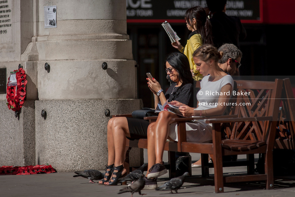 Young women sit reading at Bank triangle in the City of London, UK.