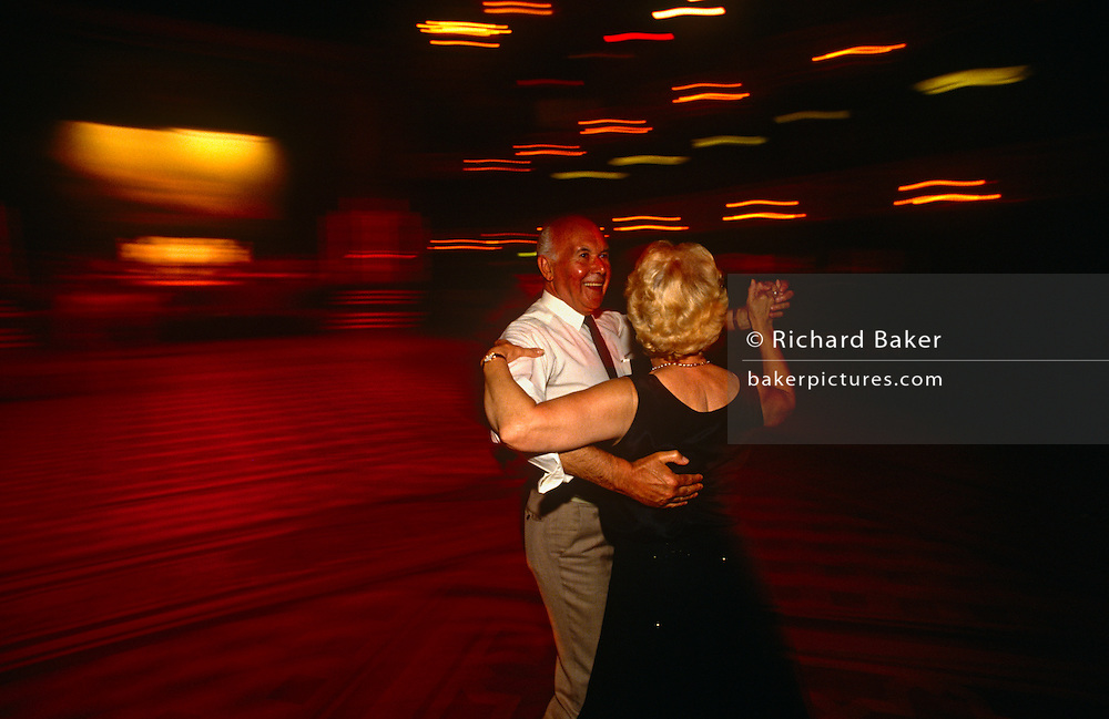 An elderly retired couple dance on the wide but darkly lit dance floor at Blackpool Tower Ballroom, England. They are the only dancers in the empty dance space, except for the Wurlitzer organist who is playing his accompanying music at the front of the stage, in a pool of bright light. We are looking down from a balcony high above and the husband and wife are pausing during their dance routine, stopping just long enough to register as sharp figures in the picture. The light is orange and red because of the tungsten light source. The Ballroom is the traditional home of the mighty Wurlitzer Organ and complemented by the 3 Deck Wersi - the world's most advanced organ. The Wersi is a state-of-the-art Louvre organ which is played by the resident organists in this magnificent setting. The present interior of the Blackpool Tower circus  was created by the famous theatre designer, Frank Matcham and completed in 1900.