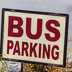a small brown and white bus parking sign.