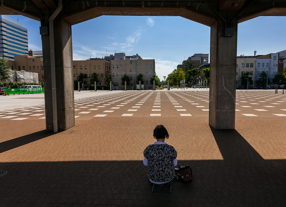 An older Japanese woman sits in the shadows of Yamashita Rinko Line promenade to sketch in Minato Mirai, Yokohama, Japan.  Friday September 12th 2014
