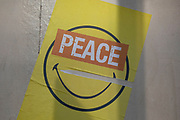 Smiley face street art paste up with a positive message in London, United Kingdom.
