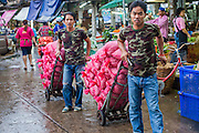 09 OCTOBER 2012 - BANGKOK, THAILAND: Porters deliver nuts to a shop in the Bangkok Flower Market. The Bangkok Flower Market (Pak Klong Talad) is the biggest wholesale and retail fresh flower market in Bangkok. It is also one of the largest fresh fruit and produce markets in the city. The market is located in the old part of the city, south of Wat Po (Temple of the Reclining Buddha) and the Grand Palace.    PHOTO BY JACK KURTZ