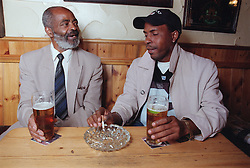 Father and son sitting at table in pub drinking beer and smoking cigarette,