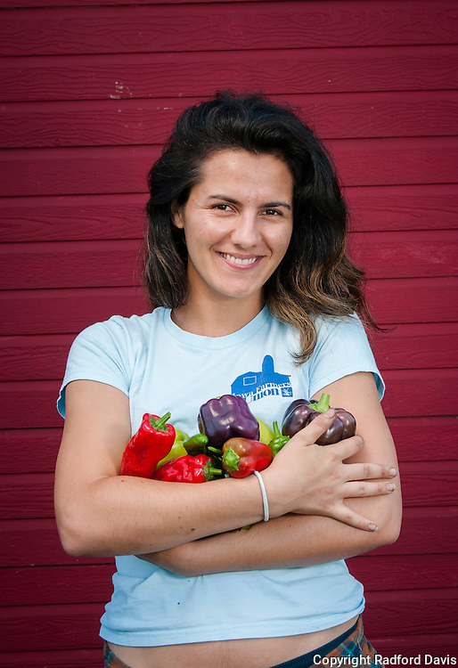 A woman holds a bounty of peppers from the small Iowa farm.