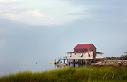 An old beach cottage sits on the water behind a field of grass