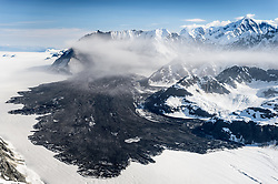 """A 4,000-foot-high mountainside released approximately 120 million metric tons of rock in 60 seconds during a landslide onto the Lamplugh Glacier in Glacier Bay National Park and Preserve. In an interview with the Anchorage Dispatch News, geophysicist Colin Stark of Columbia University's Lamont-Doherty Earth Observatory, described the slide as """"exceptionally large."""" He compared the massive landslide to roughly 60 million medium SUVs tumbling down a mountainside.<br /> <br /> The slide occurred on the morning of June 28  in a remote area of Glacier Bay National Park in southeast Alaska. It was first observed by Paul Swanstrom, pilot and owner of Haines-based Mountain Flying Service. Swanstrom noticed a huge cloud of dust over the Lamplugh Glacier during a flightseeing tour of Glacier Bay National Park several hours after the slide occurred. Swanstrom estimates the debris field to be 6.5 miles long, and one to two miles in width.<br /> <br /> Even two days later, as this aerial photo of the Lamplugh Glacier landslide shows, a dust cloud remained over the unstable mountainside due to still tumbling rock."""