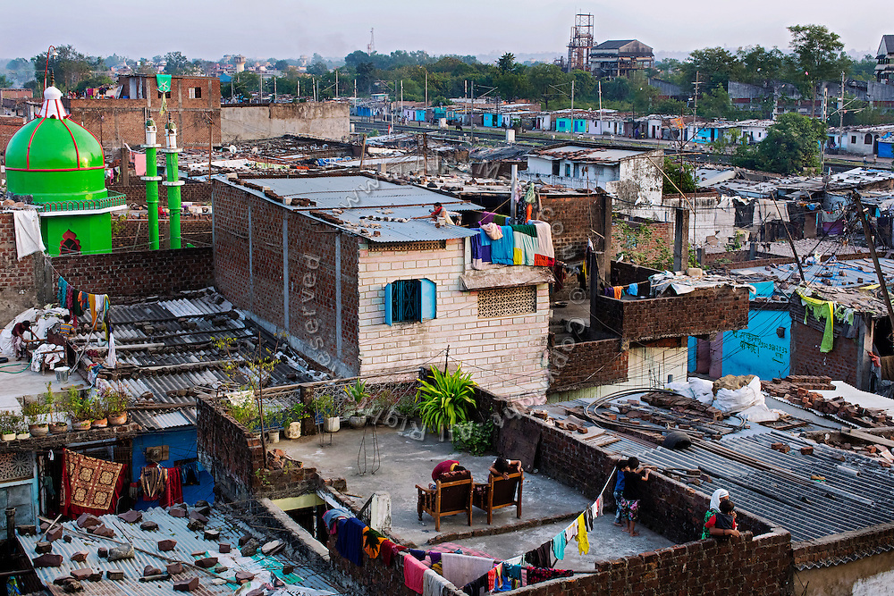 A woman is collecting her dry laundry while neighbours are enjoying a fresh afternoon on the roofs of their homes, standing next to the abandoned Union Carbide (now DOW Chemical) industrial complex, (visible in the top/right) site of the infamous '1984 Gas Disaster' in Bhopal, Madhya Pradesh, central India.