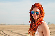 Portrait of a pretty redheaded woman at the beach.
