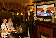 A couple watch Senator John McCain giving a hearfelt speech, conceeding defeat on a live CNN TV screen that is broadcasting live from Phoenix, Arizona the senator's conceeding speech immediately after the TV channel called Obama's victory in the 2008 US presidential elections. A life-sized cut-out of Barack Obama stands to the screen's left and the new President smiles towards the camera but his adversary, John McCain looks across the London pub as if talking to the young couple who sit without expression in this historic political election which saw the election of America's first black Commander in chief. The location is a pub called the Hoop and Toy, in South Kensington, West London which has been opened all night for this special event for the American expatriate community living in this European capital.