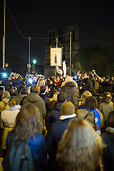 """People praying next to Notre Dame Cathedral with a statue of Virgin Mary during an evening of prayer and songs organized by Catholics community the day after Notre Dame Cathedral blaze with a march organized from Saint-Sulpice church to Saint Michel and finally next to Notre Dame Cathedral in Paris early on April 16 the day after the beginning of the fire , 2019. A huge fire that devastated Notre-Dame Cathedral is """"under control"""", the Paris fire brigade said early on April 16 after firefighters spent hours battling the flames. Photo by Raphael Lafargue/ABACAPRESS.COM"""