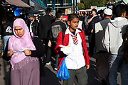 Walking home from school. People from various ethnic backgrounds around the market on Whitechapel High Street in East London. This area in the Tower Hamlets is predominantly Muslim with just over 50% from Bangladeshi descent. This is known as a very poor area of London's East End.