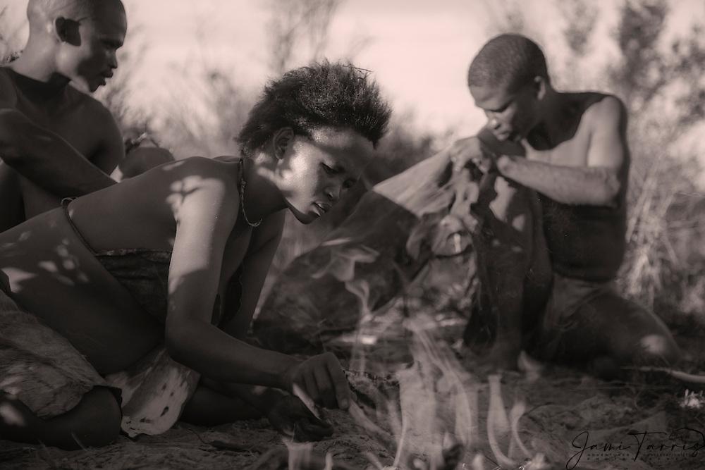 San bushmen of the Kalahari building a fire together on a cool winter day, Sepia,Kalahari, Botswana, Africa