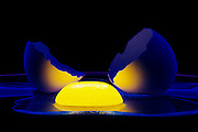 The glowing yolk of a cracked egg on a plater illuminutes the two halves of its shell.Black light