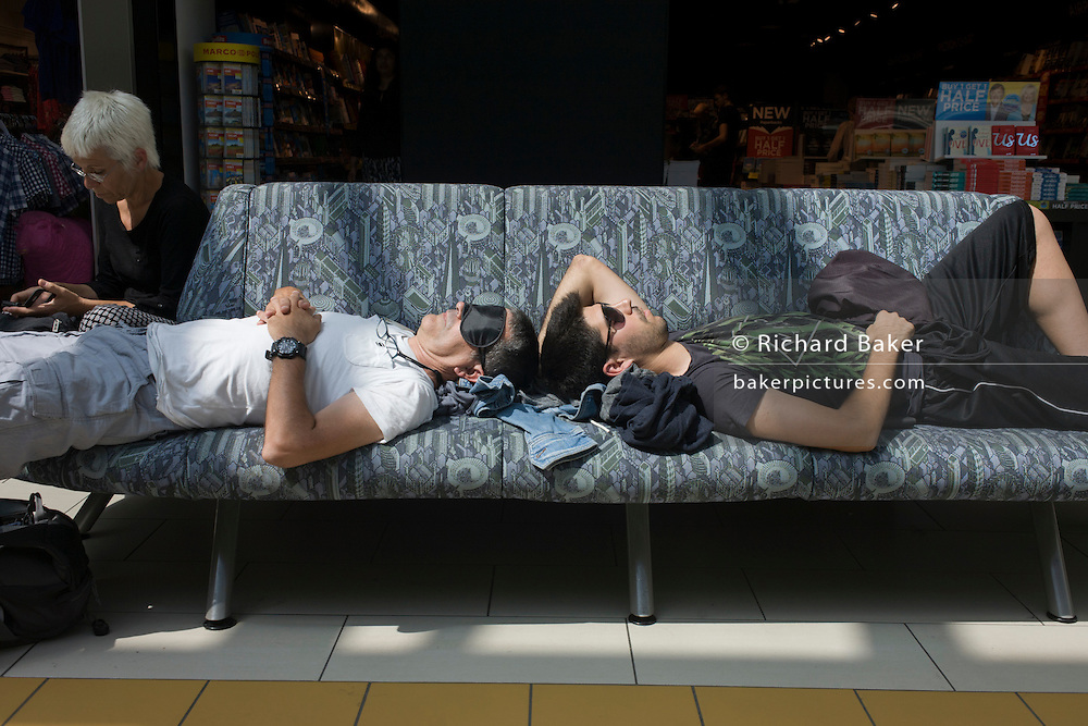 Passengers stretched out on an airport terminal seat at Gatwick, London.