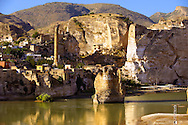 Remains of medieval Artukid Old Tigris Bridge – Built in 1116 by Artukid Fahrettin Karaaslan, the biggest in Anatolia at the time, with the old town Hasankeyf and its ruins on the cliffs abover the river Tigris. The minaret is of the El Rizk Mosque built 1409.  Turkey. 7 .<br /> <br /> If you prefer to buy from our ALAMY PHOTO LIBRARY  Collection visit : https://www.alamy.com/portfolio/paul-williams-funkystock/hasankeyf-turkey.html<br /> <br /> Visit our PHOTO COLLECTIONS OF TURKEY HISTOIC PLACES for more photos to download or buy as wall art prints https://funkystock.photoshelter.com/gallery-collection/Pictures-of-Turkey-Turkey-Photos-Images-Fotos/C0000U.hJWkZxAbg