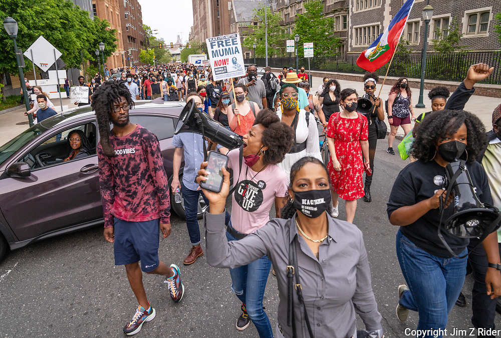 A protester chants through a megaphone as demonstrators make their way to the home of Penn's president, where the Africa family shared stories of their youth.