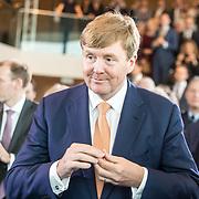 NLD/Amsterdam/20190314  - Koning bij viering 100 jaar Luchtvaart  in Nederland, Koning Willem Alexander  bekijkt het geslagen herdenkingsmuntje