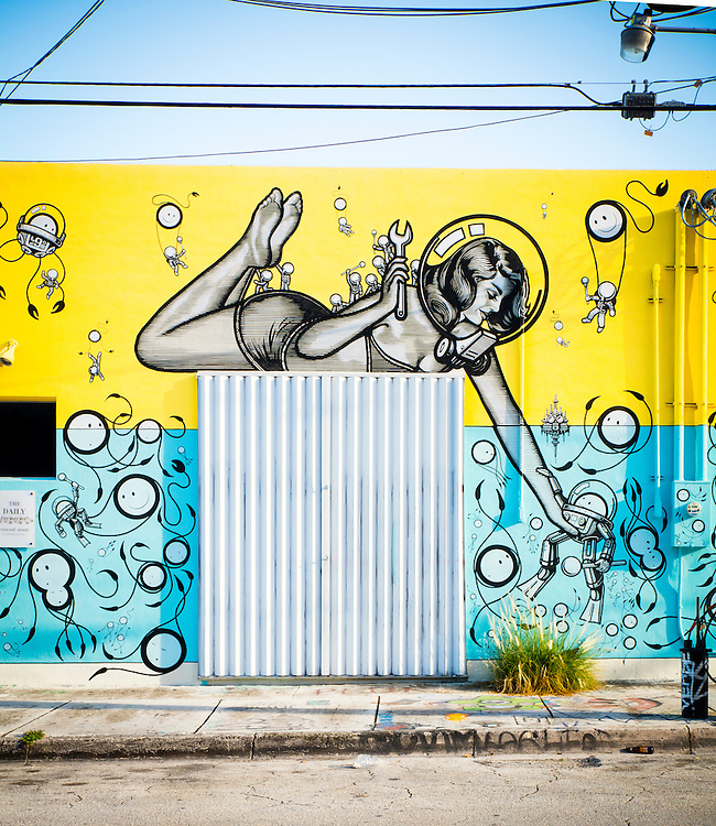 """In Miami's Wynwood district, a giant pin-up girl wears a bubble-like diving helmet and a two-piece bathing suit in a whimsical, 1950s-ish, science fiction-like mural created by an Amsterdam-based art collective known as """"The London Police."""""""