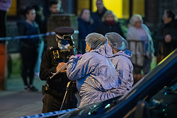 © Licensed to London News Pictures. 09/03/2021. London, UK. Forensic investigators talk to a uniformed officer after Metropolitan Police closed off Poynders Road in what is believed to be connected to the search for missing person Sarah Everard. Photo credit: Peter Manning/LNP
